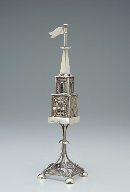 two-tiered square tower with movable flag on top on a base made of four wires extending to a square foot; each corner of the foot sits atop a small silver dome; the walls of all tiers done in openwork
