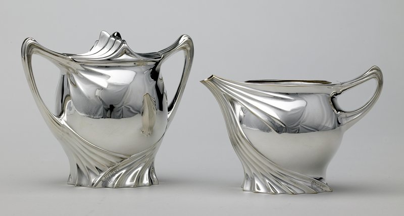 Art Nouveau style; sweeping foliate or thistle-like ribbed decoration; narrow pointed handle; wide, short spout