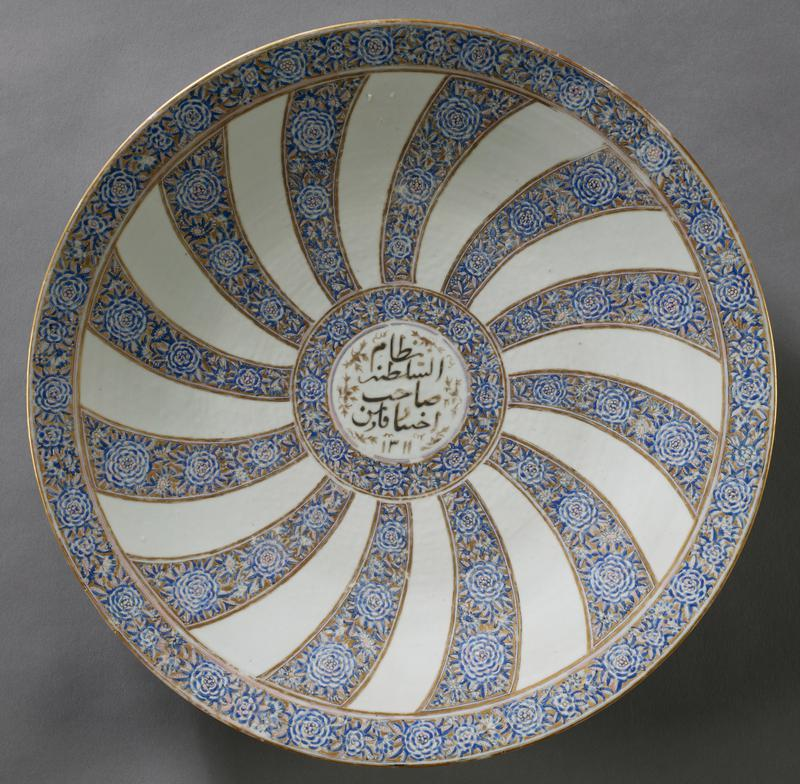 large plate on wide ring foot; white on bottom; radiating curved bars of blue and white flowers extend from flower-encircled central medallion with black Arabic text