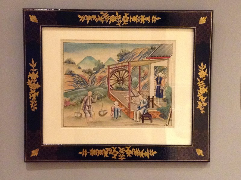 standing woman with child at R; seated man splitting a reed or twig, LRC; man in LLC carries a yoke; small figure seated between the two men; black, gold and red lacquer frame