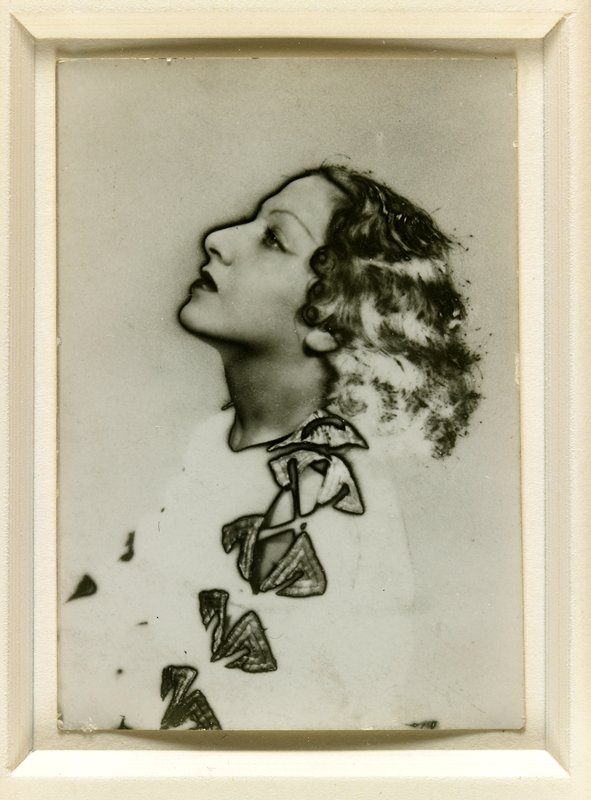 woman in profile from PL, looking up, with wavy hair; metallic-look sleeve details; framed in wood, tortoise shell and mother-of-pearl frame with checkerboard corners