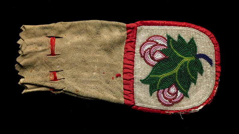 small pouch with red ribbon drawstring and trim; bottom beaded on both sides: red fruit with leaves and stem on one side, green leaf and red organic forms on other side--both on ground of clear beads