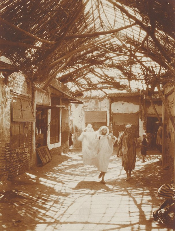 two men walking in an alley covered by a twig and thatch roof; youth and other figures in background