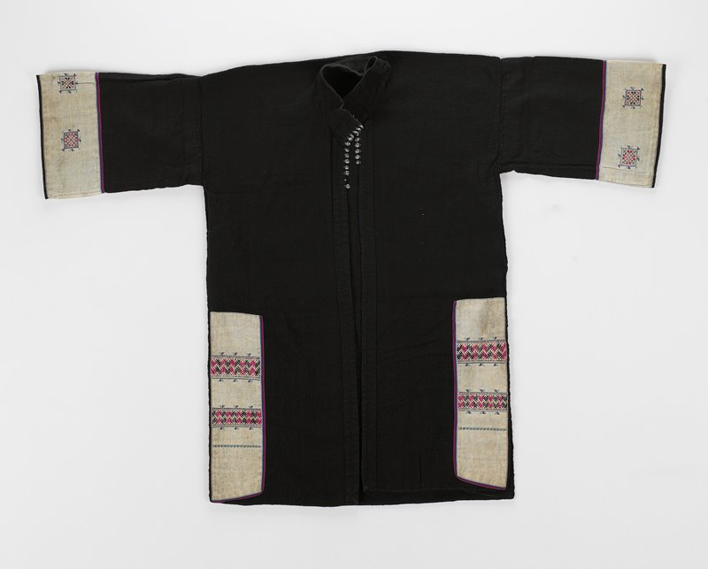 "black hand-woven cotton jacket with needlepoint and metal trim at neck; jacket has stand-up collar and side slits; cuffs and sides have white 3-1/4"" embroidered panels; unlined"