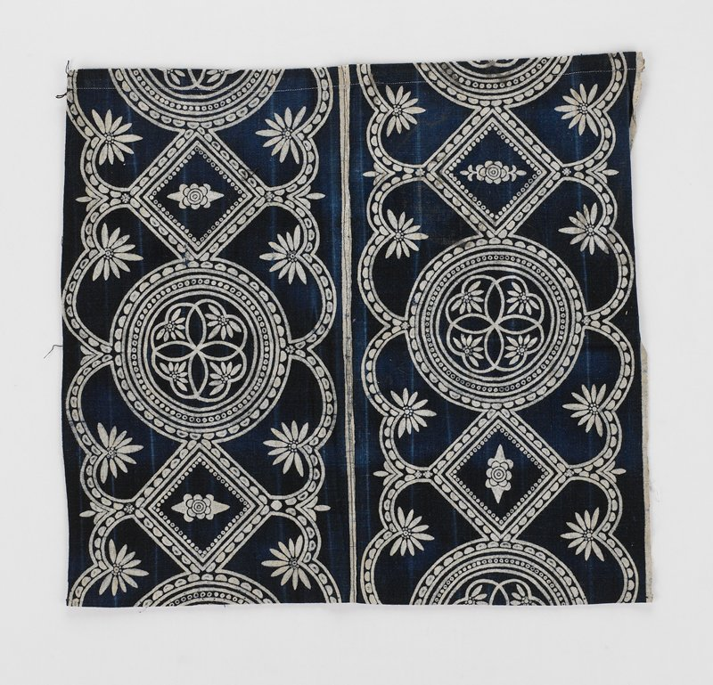 small, vertical seam; large batik print in dark blue and white; large circular and floral pattern; three sides machine hemmed
