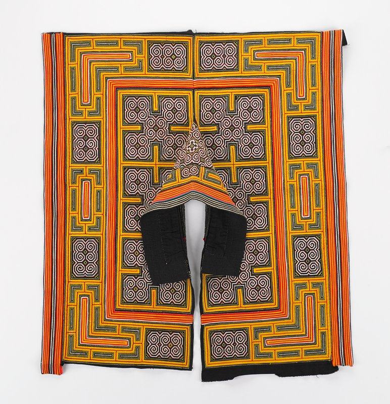 appliqued and embroidered strong geometric patterns in yellow, black, red and white; open at front with high stand-up collar cape; very bright