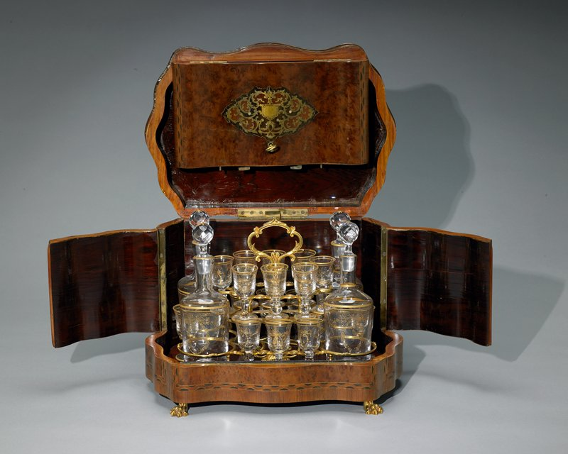 wood tray with scalloped ends; metal holders for glasses and decanters: four circular decanter holders; two levels of glasses holders, eight on bottom level and eight on upper; upper level glasses rest on metal holder with star cut-outs in base handle at top to left tray