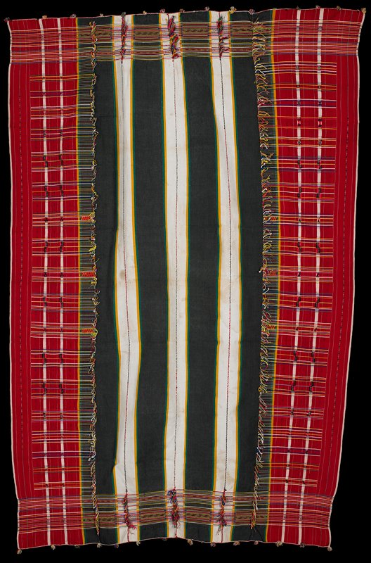 three white stripes run length of wrapper, alternating with black; multi-colored crossing patterns over red run down the edges and hang through the weave in areas