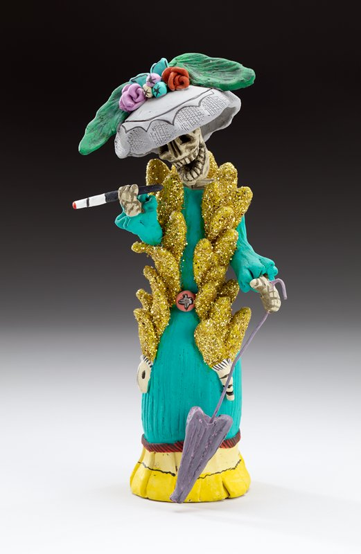 standing skeleton dressed in green and yellow long dress with gold glitter-covered scarf and grey hat with flowers and large green bird's wings; purple parasol in PL hand and cigarette in holder in PR hand; spring at neck