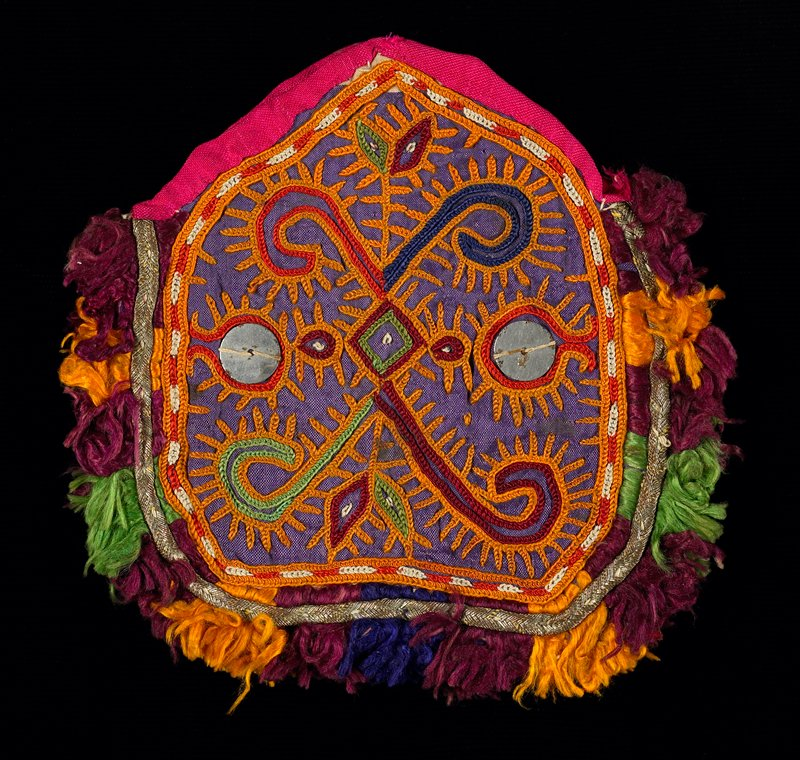 "orange, purple; small; two shi-sha mirrors decorate ""X"" chain stitch design; outlined in metal braid and multicolored silk fringe; pink tape wraps around the inverted ""V"" opening at top; both sides identical designs"