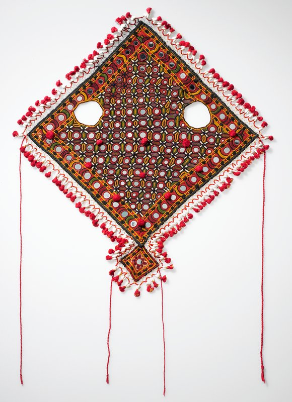 diagonal square with eye holes; overall embroidery has circles with metal mirror centers; red pompoms on main body and at ends of white shell-like tassels attached to all sides of main body with glass bead holders; small diagonal square on nose end; red twisted ties at sides and on nose piece; black, gold, green, purple, red and white embroidery