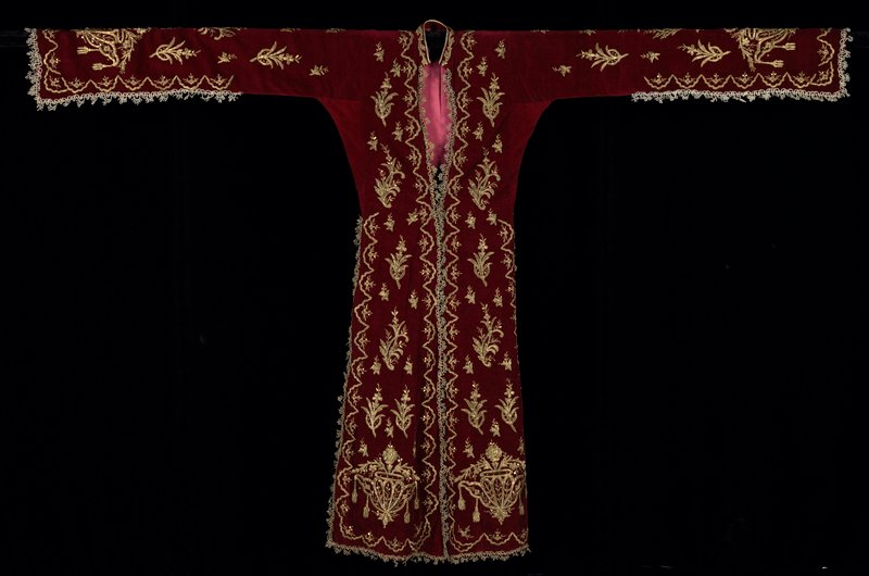 gold is intact; maroon velvet; coat dress with very deep side vents and very long rented sleeves, lined in dark rose satin; heavy embroidery throughout in floral motifs; front edge and vents have elaborate silver edging; stand-up collar; underarm gussets