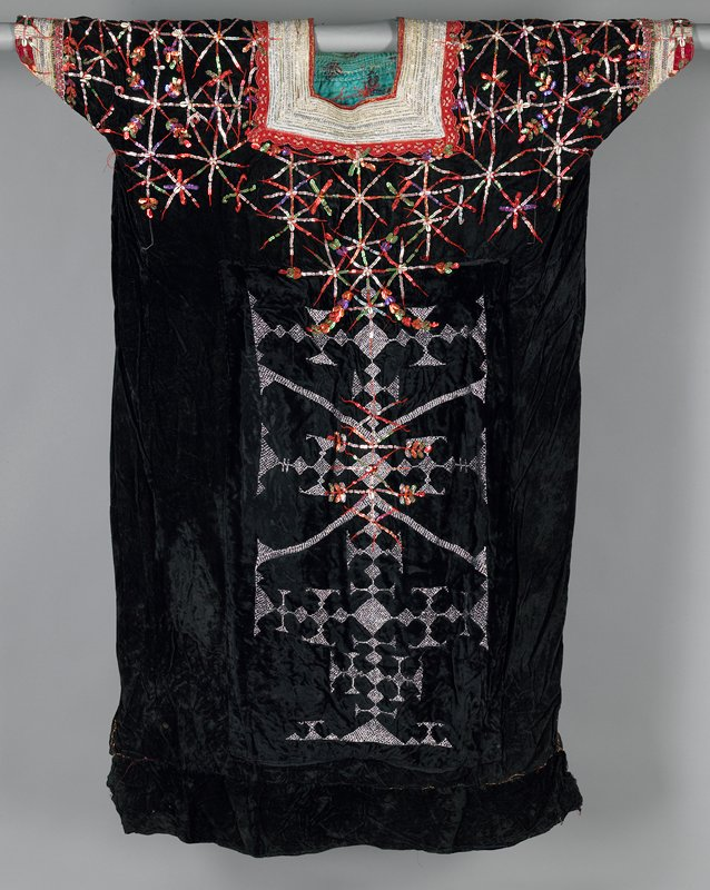 long, black velvet loose dress with heavily embroidered cuffs in silver, gold and red metallic thread; short raglan sleeves; front of dress and upper back has embroiderey with silver thread, colored sequins and cowrie shells in criss-cross, diamond and floral patterns; lined square neck has wide edging of silver thread and sequins, and red and gold lace; lower back edge is pieced and is shorter than front (long front section and sides are pieces below sleeve line)