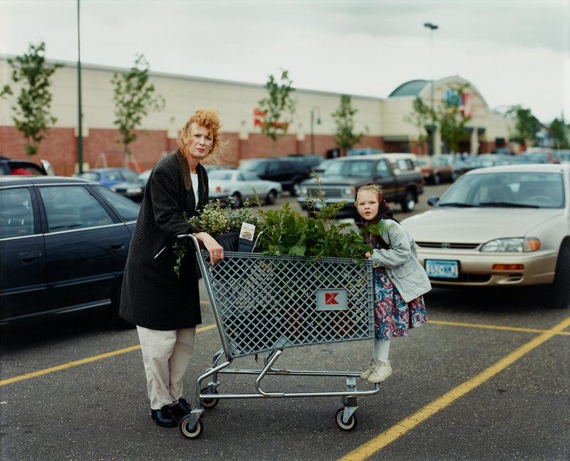 woman with shopping cart full of plants in Kmart parking lot with girl standing on end of cart; framed behind plexi; white frame