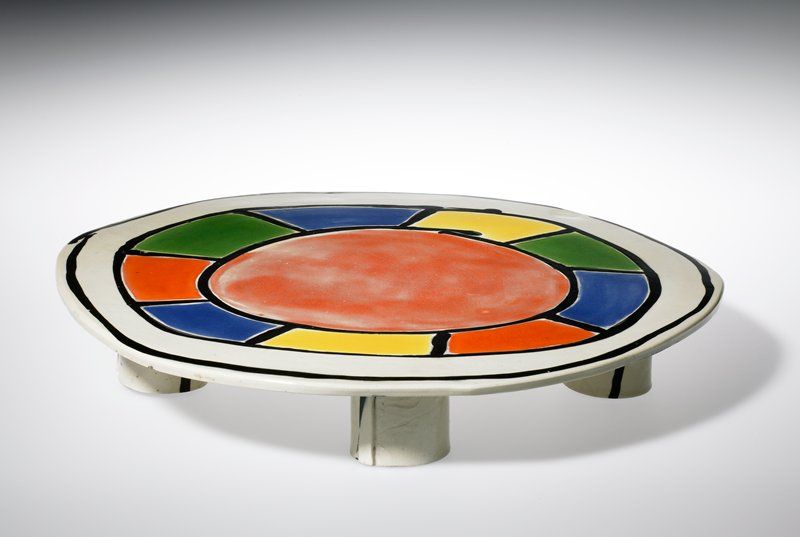 disc with five straight tubular legs; top decorated with multicolored geometric design with black borders; black lines and arcs on bottom