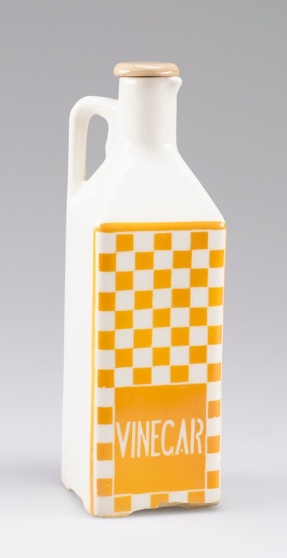 "square body; short round neck and small spout; squared-off handle; white porcelain with one side decorated with yellow-orange checkerboard and ""VINEGAR"" in white; small stopper"