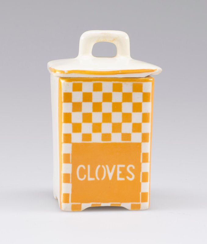 "small square container with cover with small handle; white porcelain decorated with yellow-orange checkerboard and ""CLOVES"" in white on front; stripe around edge of cover on front and sides"