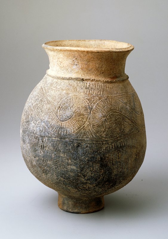 Round-bodied jar on a small foot; wide, slightly flaring mouth; decorated with incised swirls and hatching; unglazed; Ban Chieng ware