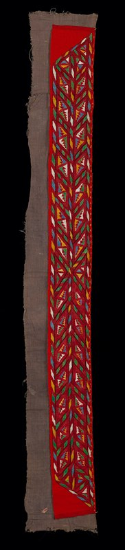 fine embroidery of geometric shapes in running strip to form a collar; done in red, yellow, green and blue yarn on red wool banat face; beige cotton backing is pieced and larger than embroidered part