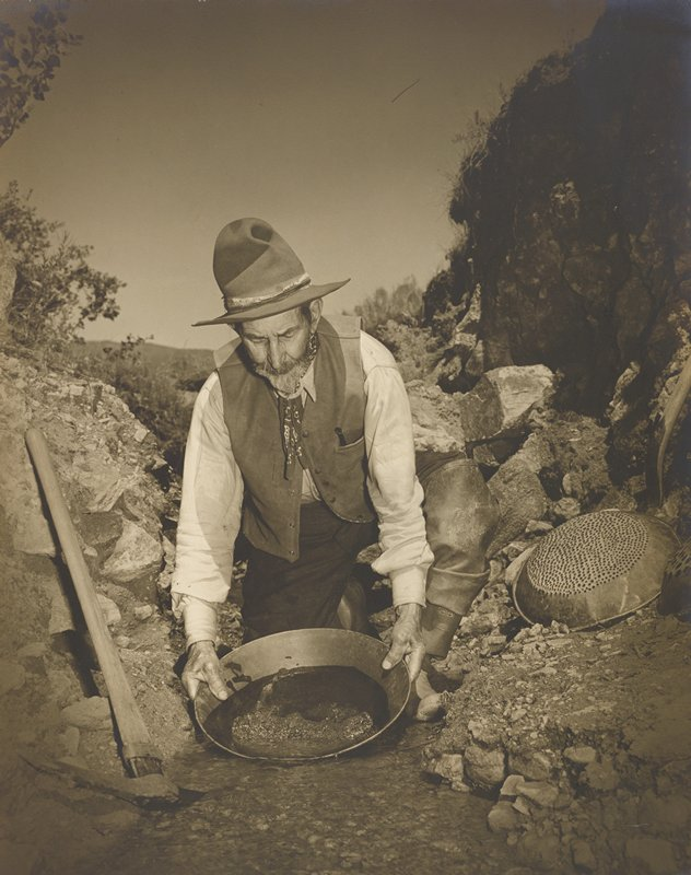 bearded old man, wearing a vest, neck kerchief and a hat, panning for gold in a stream; strainers on rocks at R, pick axe at L