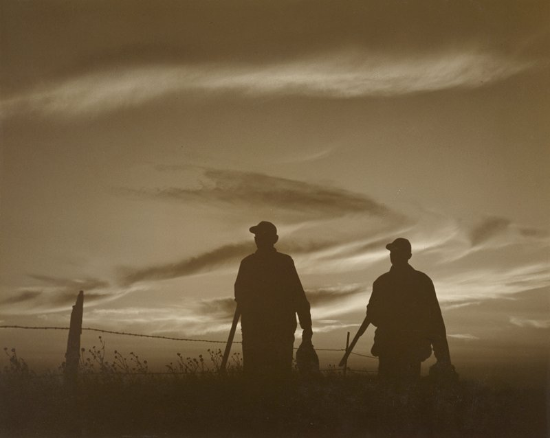 silhouettes of two hunters with rifles, wearing caps; fence behind men; sky at sunset