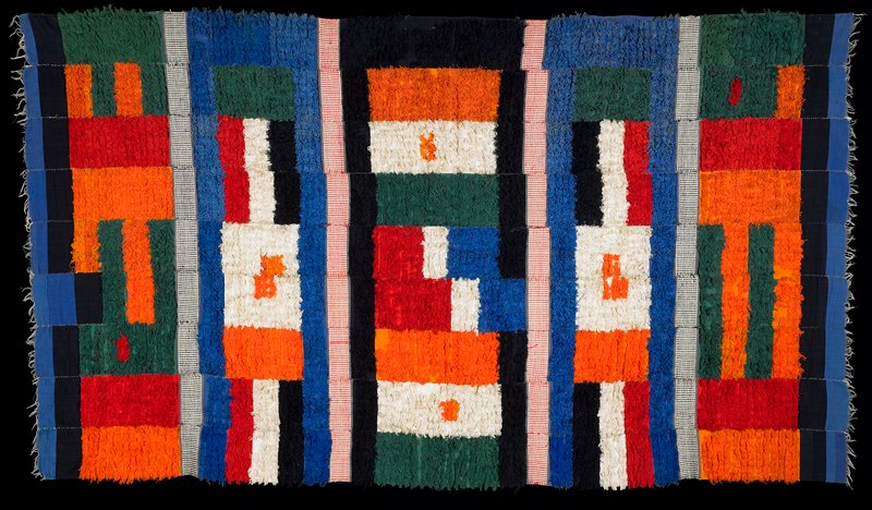 nine strips sewn together; five pile bands in rectangle and bar designs in multicolors, separated by strips with dot pattern in red or black on white; black and blue ends
