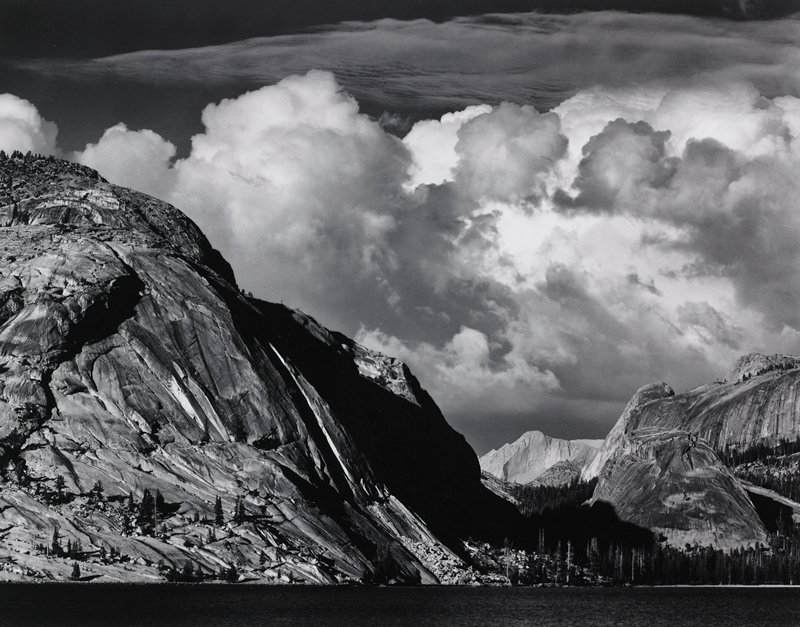 band of water at bottom; rocky mountain peaks with evergreen trees behind water; large clouds in sky