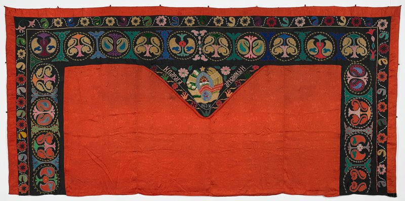 "black bands at top and sides with central triangular overlay; red at center and red trim; bands embroidered with outer running flower pattern and inner organic medallions in multicolors; triangular section embroidered with a seal with a sunset over mountains, cotton, wheat and a hammer and sickle; ""1962"" below seal"