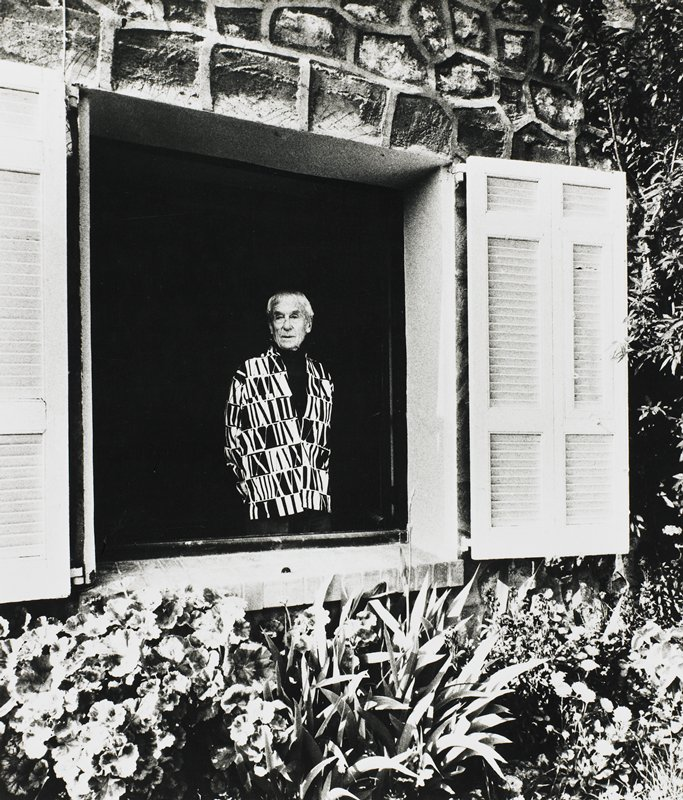 old man with white hair wearing a black and white graphic shirt with Roman numerals, standing looking out of a shuttered window onto a garden