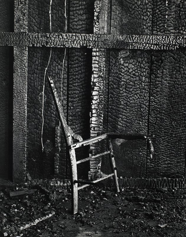 side and front of a wooden chair, leaning against a burned wooden wall