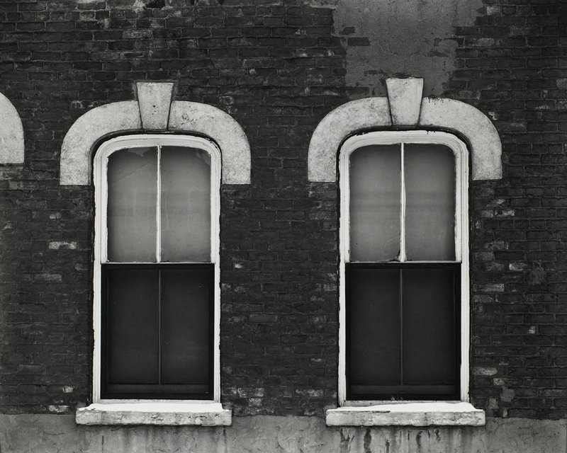 two windows in a brick building; curved on top, with curved lighter-colored element above and light-colored keystone