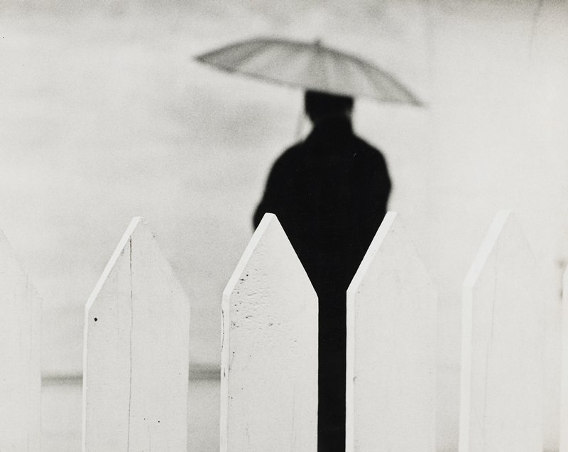 top of a white picket fence; dark figure, seen from back, holding an umbrella, on other side of fence