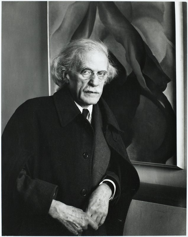 portrait of a man with white hair and moustache and round glasses, wearing a dark coat; man stands in front of a flower painting by Georgia O'Keefe