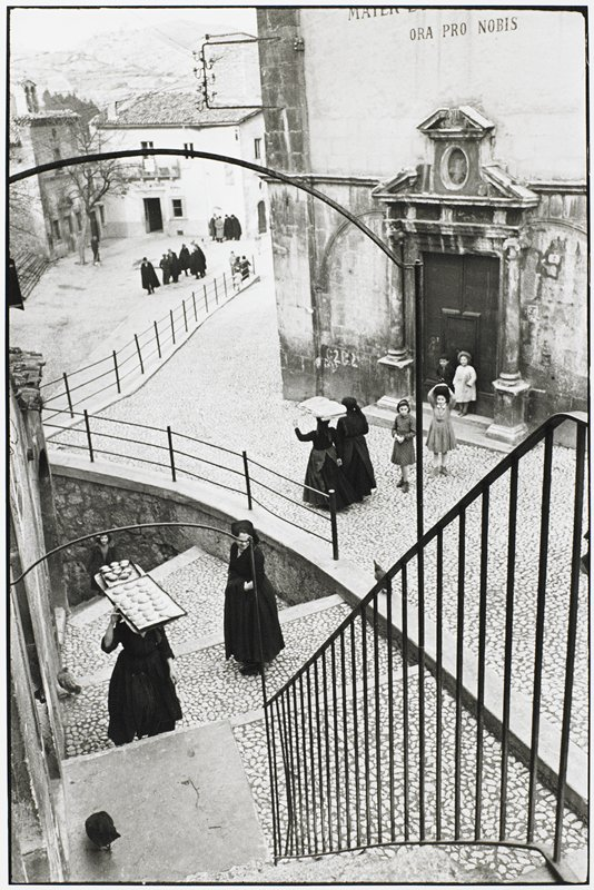two black robed women carrying bakery goods on heads; three young girls outside church; hillside street descending