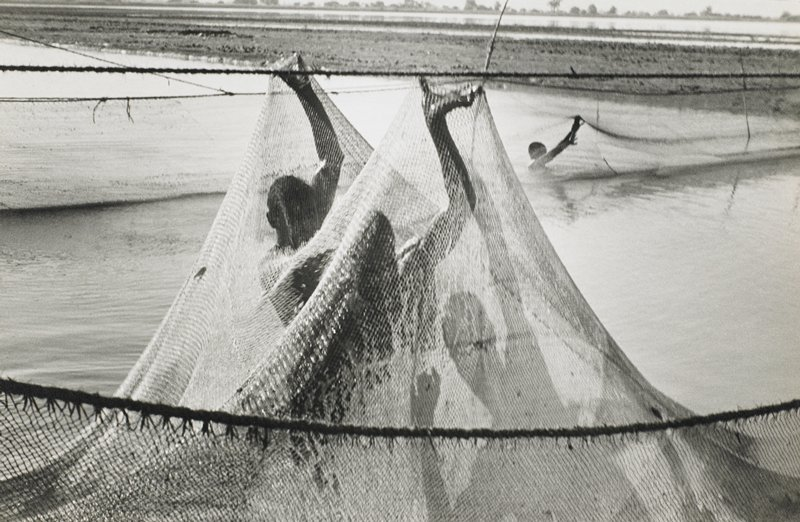 two figures and a shadow figure with large net in river