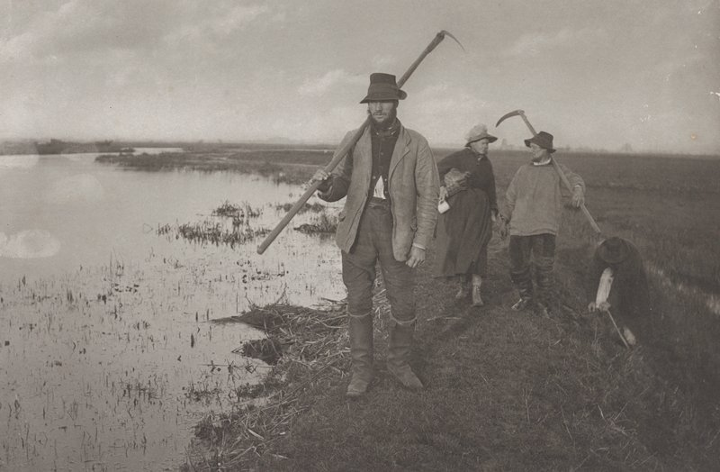 standing man on the bank of a marsh, wearing a hat, boots and coat, with a sickle; woman with jug and another man with sickle behind first man; third man tying his shoe at R