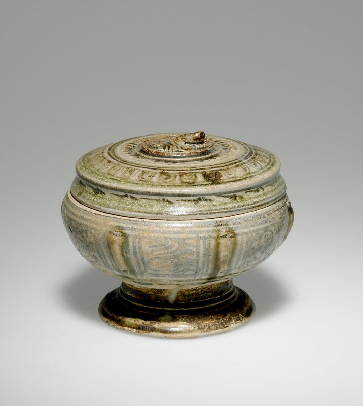 vessel on raised wide foot; rounded body; flat top; organic moulded decorative top knob; moulded ribs on body; cream-colored with blue, brown and green rings and organic designs; cartouches on sides