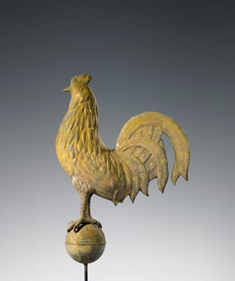 rooster standing on a ball with rib at center; gold patina