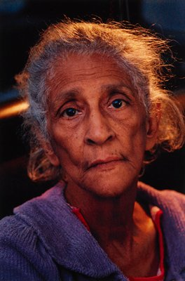 portrait of head and shoulders of older woman with grey hair wearing purple sweater; matted